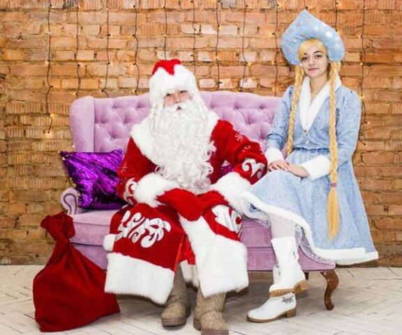 Снегурочка с Дедушкой Морозом дарят подарки.